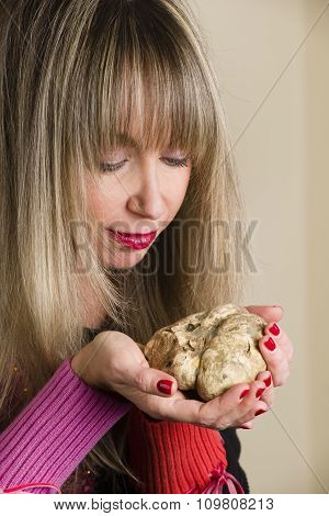 White Truffle In The Hands Of A Woman Who Looks At It