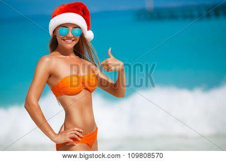 Maiden in orange bikini and hat of Santa Claus