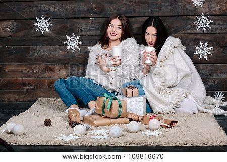 two girls drinking hot beverage