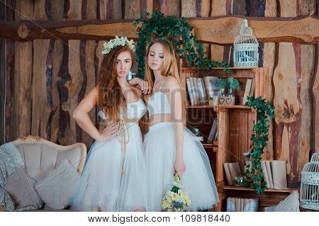 Two beautiful sensual brides standing in vintage interior holding flowers