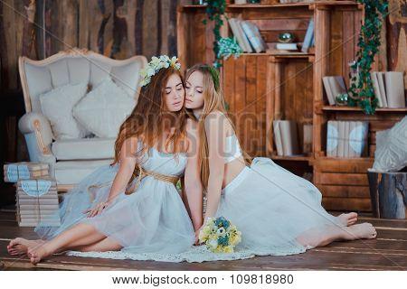 Two beautiful sensual girls sitting in vintage interior