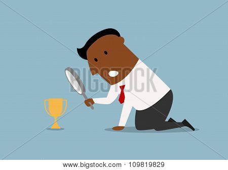 Businessman looking at small trophy with magnifier