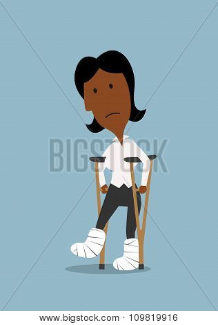 Unhappy businesswoman walking on crutches