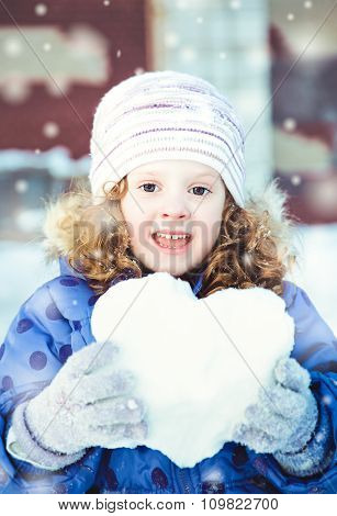 Beautiful Little Girl Happily Playing Snowballs In Winter Park On Bokeh Background With Snowflakes.