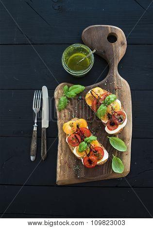 Tomato, mozzarella and basil sandwiches on dark wooden chopping board, pesto jar, dinnerware over bl
