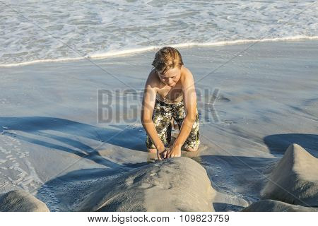 Young Boy  Enjoys Playing At The Sandy Beach