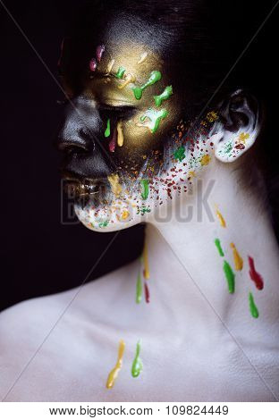 woman with creative make up closeup like drops of colors, facepaint close up halloween style