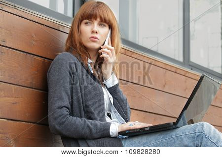 young woman with smartphone and laptop