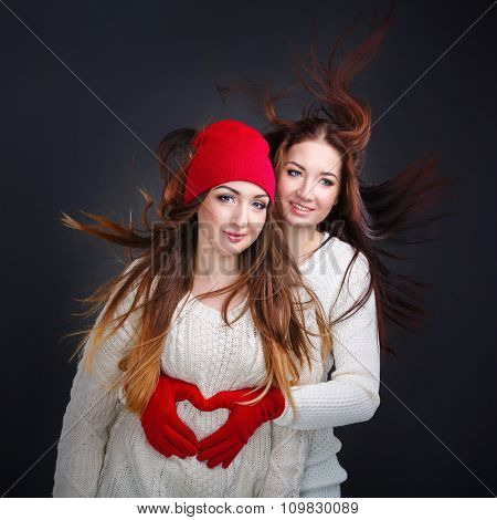 Girlfriends Hugging In A Warm Sweater. Heart From Fingers.