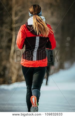 closeup young woman runner running on snow-covered alley in a winter Park