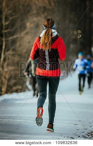young woman runner running on snow-covered alley in a winter Park. rear view