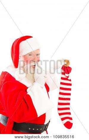 Santa Filling A Stocking On White