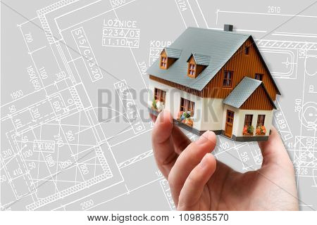 hand holding new model house and architecture blueprint plan