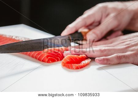 Cook cutting fresh salmon fillet