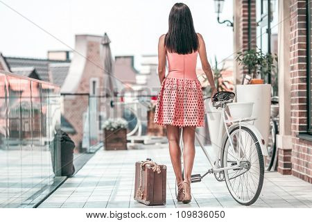 beautiful Brunette woman with bicycle and suitcase