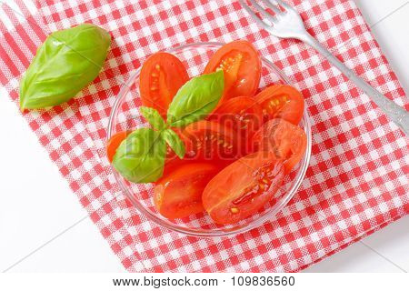 Halved fresh oval-shaped red tomatoes