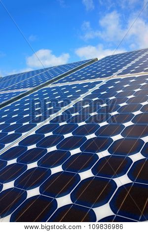 Closeup on solar panels capturing the sunlight over a blue sky