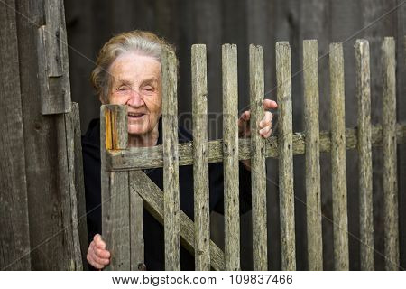 An old woman near a fence in the village.