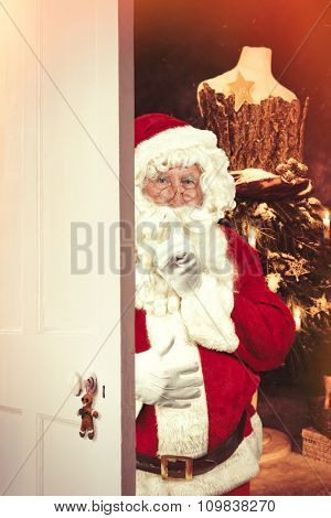 Santa Claus saying shush at open door leading to festive Christmas setting