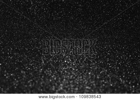 Black glitter background with christmas lights.