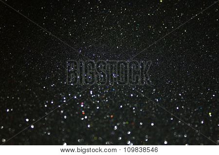 Glittering black background. Twinkling glitter particles.