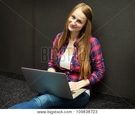 Young girl sitting on floor and laptop in her hands