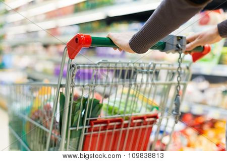 Close-up of a woman driving a shopping cart in a supermarket