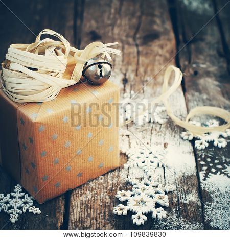 Holiday Gift With Jingle Hand Bell On Wooden Background. Toned