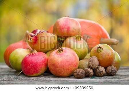 Fresh autumn fruits, apples and pomegranates, on a wooden table