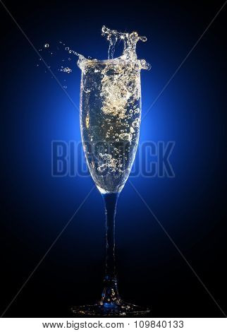 Glass of champagne with splashes and bubbles on blue background