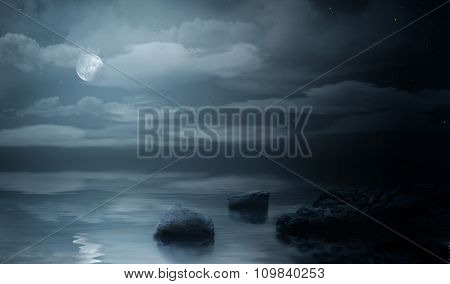 Night sea under cloudy sky