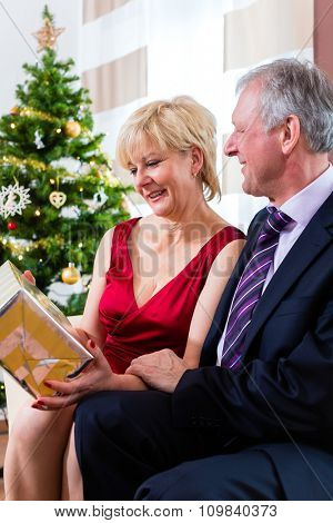 Senior man and woman celebrating Christmas with presents and X-mas tree
