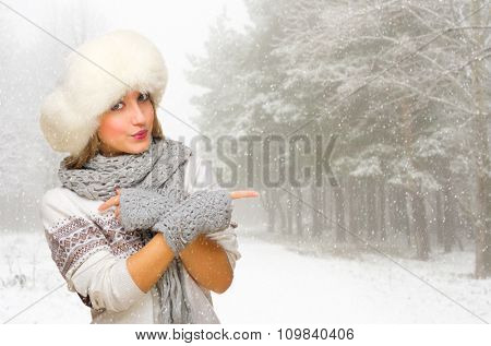 Young girl at snowy forest shows pointing gesture