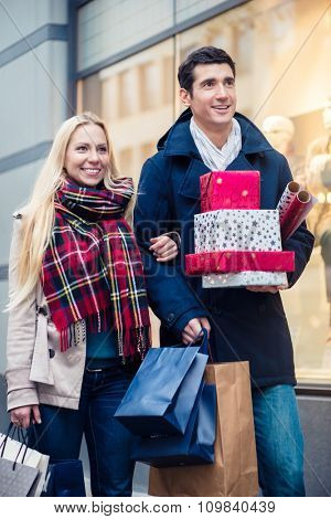 Woman and man with Christmas presents in city
