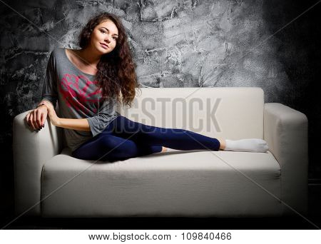 Portrait of young girl on sofa in dark room