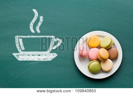 sweet french macarons and drawn cup of coffee on chalkboard
