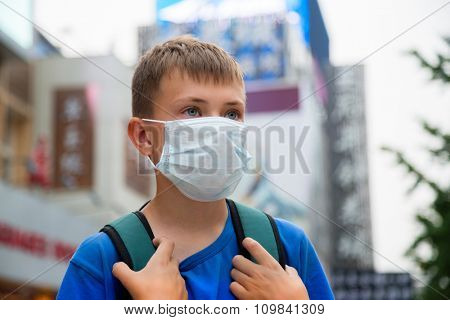 European boy in a protective mask on a street in Beijing, China.