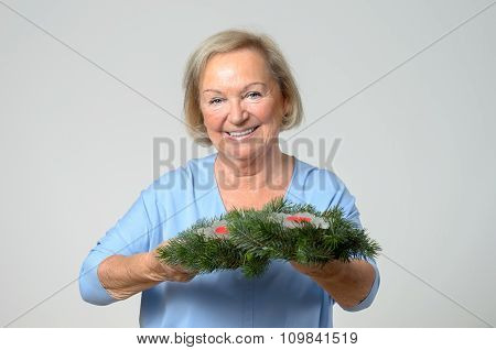 Senior Lady Holding A Christmas Decoration