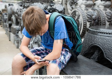 Caucasian boy using a smartphone on the famous Panjiayuan Antique Market