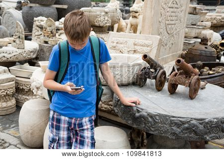 European boy using a smartphone on the famous Panjiayuan Antique Market in Beijing