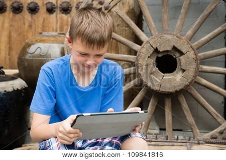 European boy used tablet PC being in the famous Panjiayuan Antique Market in Beijing