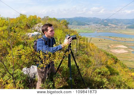 Photographer on top of a mountain on the camera shoots landscape