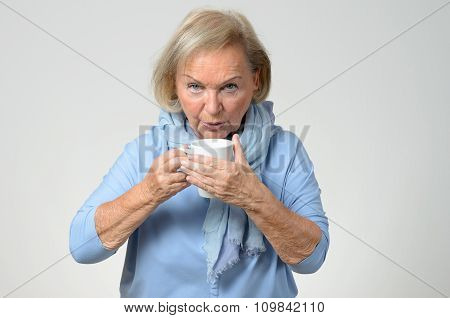 Elderly Woman Enjoying A Hot Cup Of Coffee