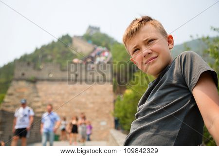 Cute boy stands on the Great Wall of China