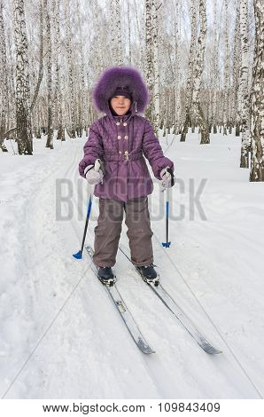 Winter portrait of the girl of four years on skis