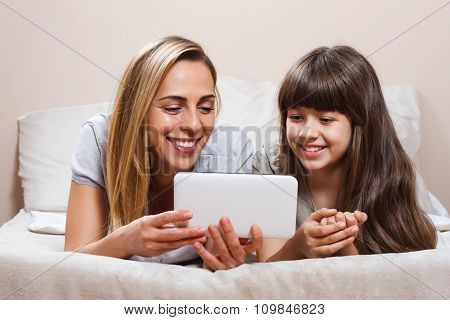 Mother and daughter using digital tablet in bed