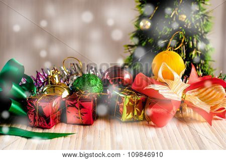 Gift Box Against A Christmas Tree On Wood Background With Snow White Drop