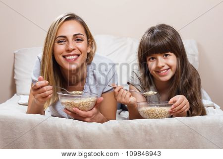 Healthy breakfast in bed for mother and daughter