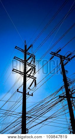 Silhouette Of Electricity Post In Dark Blue Sky Background
