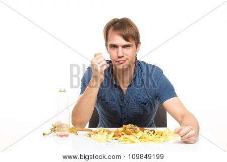 man eating a banana. on the table a lot of dirt and debris. isolated on white background